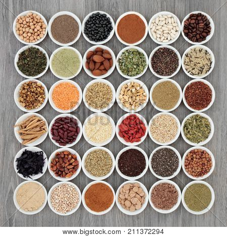 Dried diet super food with grains, cereals, legumes,  supplement powders, fruit, seeds, nuts and herbs used as appetite suppressants. Foods high in omega 3, antioxidants, fibre and vitamins. Top view.