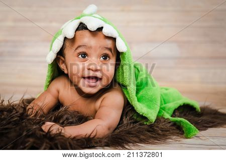 Infant dogla boy wearing bath robe laying on his tummy belly fluffy furry throw wooden background modern studio shoot modern look