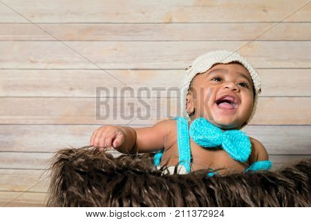 Infant dogla boy wearing hat and bow tie sitting in a fluffy furry basket wooden background modern studio shoot vintage look laughing