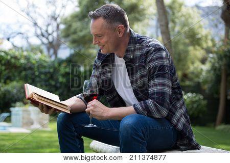 Man reading novel while having glass of red wine in garden