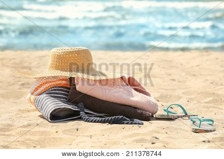 Beach towels, hat and bag on sand