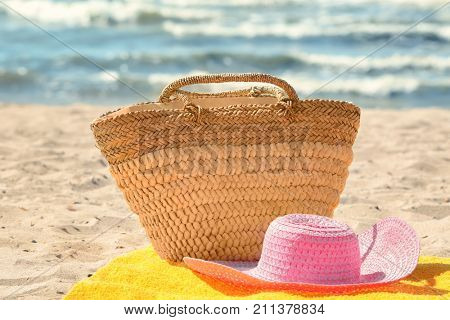 Beach towel with summer hat and bag on sand