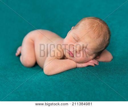 sweet newborn sleeping on stomach and hands with headband