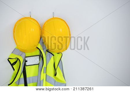 Close-up of protective workwear hanging on hook against white background