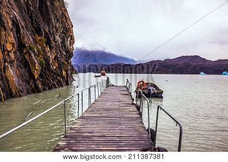 Lago Gray is a glacial lake in February. Pier for boats and pleasure boats. Torres del Paine National Park, Chile. Concept of active and exotic tourism