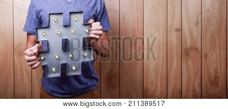 Teen holding internet hashtag symbol with lights
