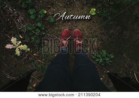 Autumn concept. Women's legs in red boots standing in autumn forest