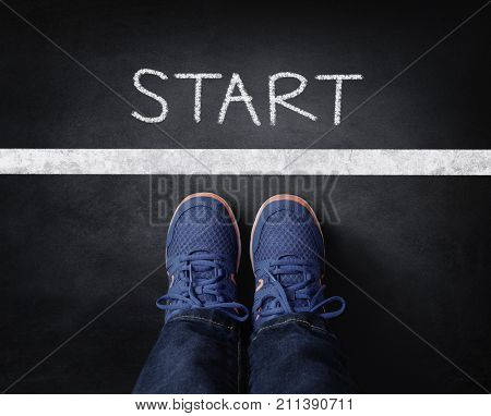 Start line child in sneakers standing next to chalk starting line on blackboard