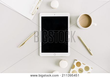 Home office desk with tablet macaroons coffee mug on pastel background. Flat lay top view lifestyle concept.