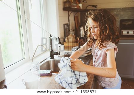 child girl helps mother at home and wash dishes in kitchen. Casual lifestyle in real interior. Teaching kids to do house work.