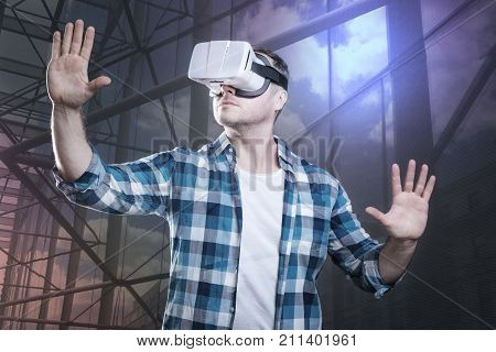Virtual walls. Clever enthusiastic young man playing a new wonderful game in his virtual reality glasses