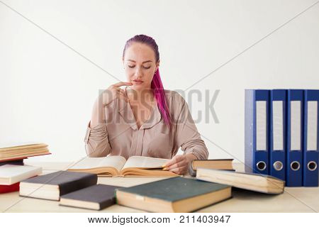 business woman with pink hair sits in the Office reads books education 1