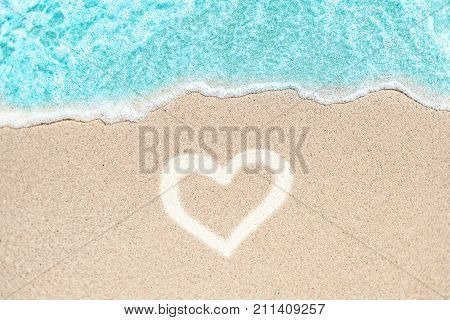 Sea Beach and Sand in summer day with love heart shape sign on sand. Blue Ocean Wave Textured Background.