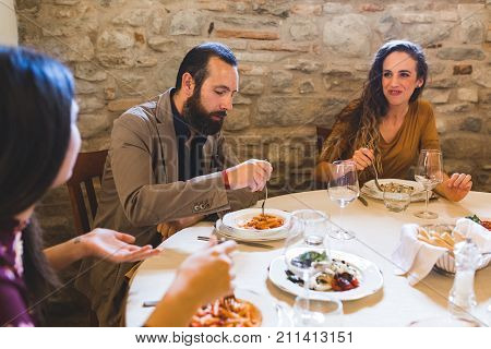 People eating pasta lunch at Italian restaurant . Three persons two women and a man sitting at the table and enjoying food together. Italian style and food in old fashioned restaurant