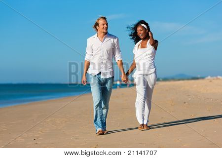 Happy couple - black woman and Caucasian man - walking and running down a beach in their vacation poster