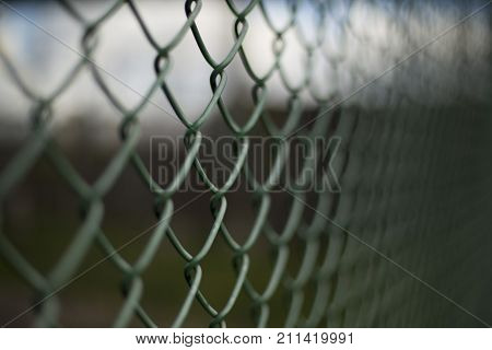 Green dark mesh fence closeup urban background