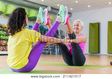 Buddy boat yoga pose by a smiling middle-aged woman and brunette girl sitting backwards in gym.