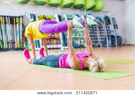 Two female fitness models doing yoga exercises, one lying on floor on mat holding legs of another above her in a sports center.