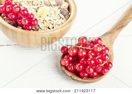 Morning breakfast muesli mix of cereals with redcurrants on wooden table background selective focus