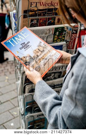 STRASBOURG FRANCE - OCT 28 2017: Woman buying Times magazine at press kiosk featuring The ISIS Caliphate Falls