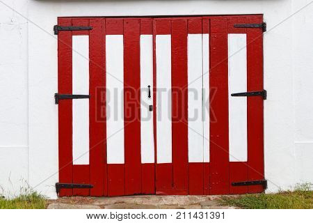 Wooden wide door of a barn painted red and white