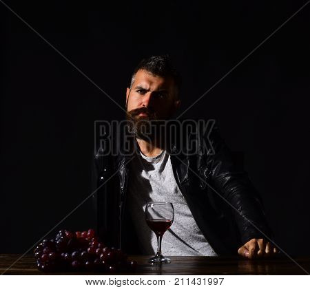 Man with beard near glass of wine on dark brown background. Winetasting and degustation concept. Sommelier tastes expensive drink. Degustator with interested face sits by wine bottle and dark grapes