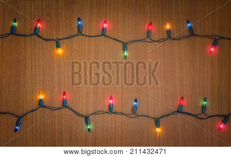 Christmas light bulbs were turned on or lid on string in multi colours; blue yellow red pink orange and green on dark teakwood background at night time Xmas or new year holiday decoration ornament concept
