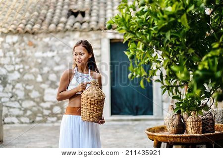 Pretty woman in ethnic Mediterranean folk traditional costume holding a rattan olive oil jug. Hospitality and ethnic tourism concept