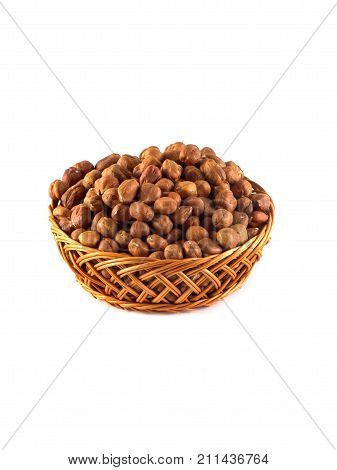 Hazelnuts with leaves in a wooden basket isolated on white background