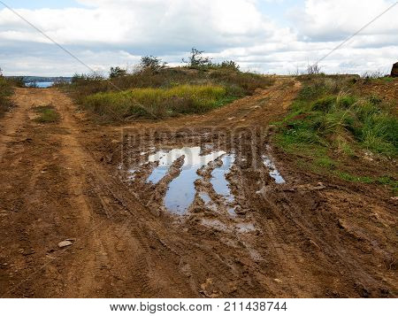Dirt Road With Puddles And Mud, Washed Out After A Rain On A Cloudy Autumn Day. Authentic Rural Land