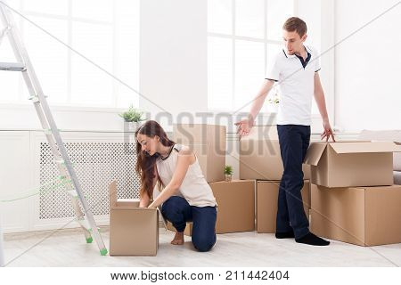 Young happy couple unpacking moving boxes in new apartment, copy space