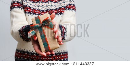 Unrecognizable woman giving christmas gift. Cropped image of girl in sweater with present box in hands, gray background. Preparing for xmas and new year, copy space