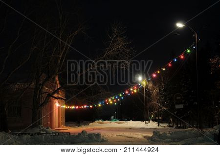 Beautiful night illuminating colorful decorative lamps suspended on post in front of building outdoor