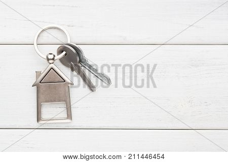 Two steel keys with house shaped trinklet on keyring on white wooden background with copy space. Home key, safety, security, real estate and rent concept, top view