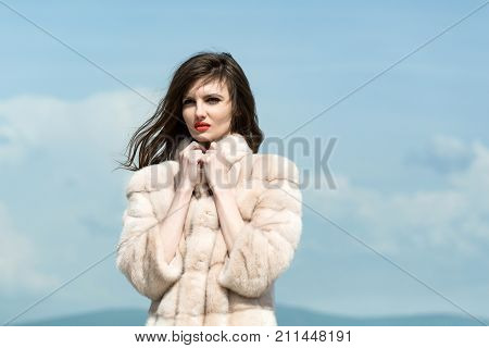 Girl in fashionable fur coat in winter. Woman with long brunette hair and red lips in coat. Fashion model on blue sky background. Beauty and winter fashion. natural faux or artificial fur.