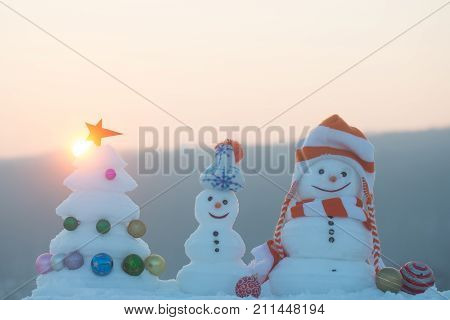 xmas tree with star and balls. Snowmen with smiley faces in hats on evening landscape. Snow sculptures on sunset sky background. Winter holidays celebration concept. Merry Christmas and happy new year