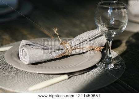 Table setting. One grey plate. Knife and fork. Old fashioned wine glass. Rustic napkin. Wooden table. Selective focus.