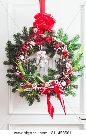 Christmas wreath hangs on the white doors. Red and white elements, bow for decorating holiday house