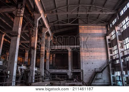 Dark industrial interior of large empty hall for manufacturing or warehousing. Abandoned factory.