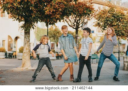 Outdoor portrait of 4 fashion kids playing together outside children dancing on the street