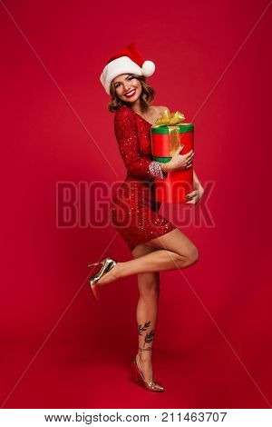 Full length portrait of a smiling pretty girl in santa hat holding present boxes while standing and looking at camera isolated over red background