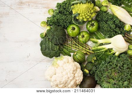 Healthy eating, assortment of green vegetables on the white wooden table, copy space for text on the left, top view, selective focus