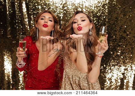 Portrait of two attractive young girls in shiny dresses holding glasses with champagne while sending air kiss and celebrating isolated over golden shiny background
