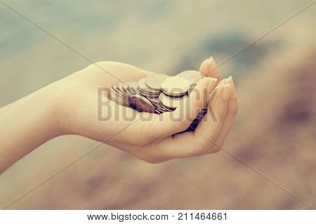 Handful of coins in palm female hands. Concept of saving and passive income.instagram toned