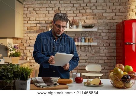 Portrait of an older man. Older man having breakfast in kitchen, reading morning news on tablet computer.