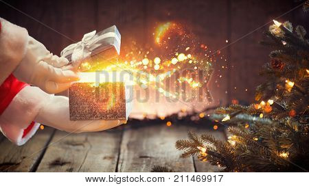 Santa Claus opens gift box, holding a gift in his hands over wooden background with blinking garland and Christmas tree. Xmas scene with magic gift, wishes