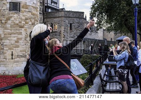 LONDON, GREAT BRITAIN - SEPTEMBER 21, 2014: Unidentified girls enthusiastically do selfies near the Tower of London.