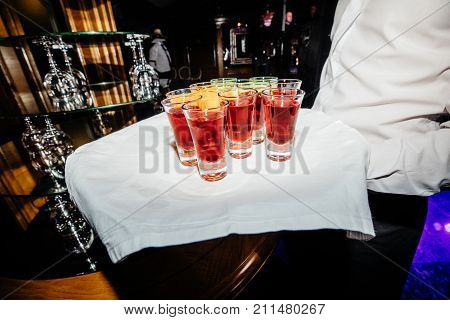 A waiter with a tray of glasses of  delicious apple punch and glasses of orange juice at the reception. Glasses with alcohol