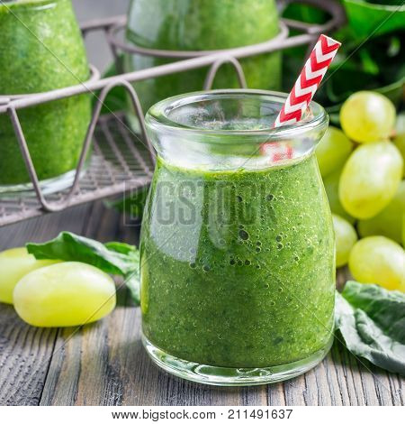 Green smoothie with spinach grape and banana garnished with raspberries in glass bottle square format