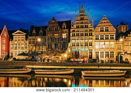 Old houses on Graslei street, canal and tourist boatds in the evening. Ghent, Belgium